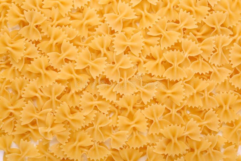 Ongekookte Italiaanse farfalledeegwaren Ruw, heerlijk en helder geel textuurclose-up Noedel, macarons, deegwaren, spaghetti royalty-vrije stock foto's