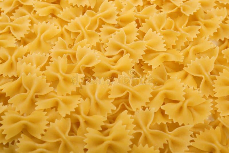Ongekookte Italiaanse farfalledeegwaren Ruw, heerlijk en helder geel textuurclose-up Noedel, macarons, deegwaren, spaghetticlose- stock afbeeldingen