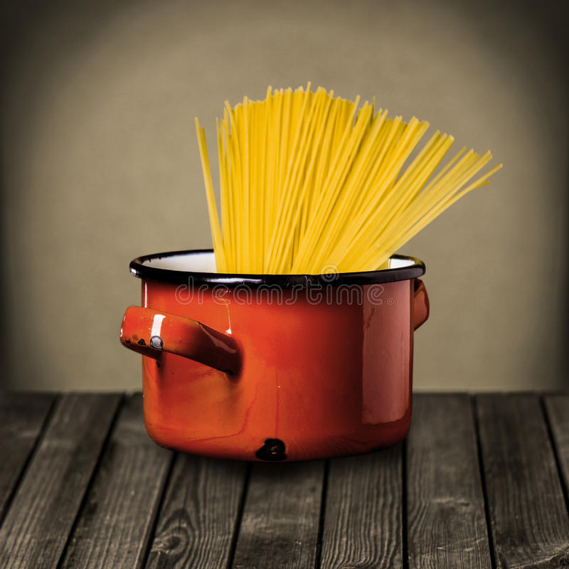 Ongekookte Italiaanse spaghetti in een rode pot royalty-vrije stock foto