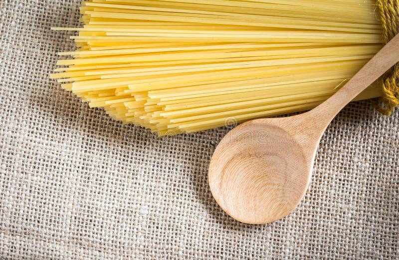 Ongekookte spaghetti en lepelhout royalty-vrije stock foto's