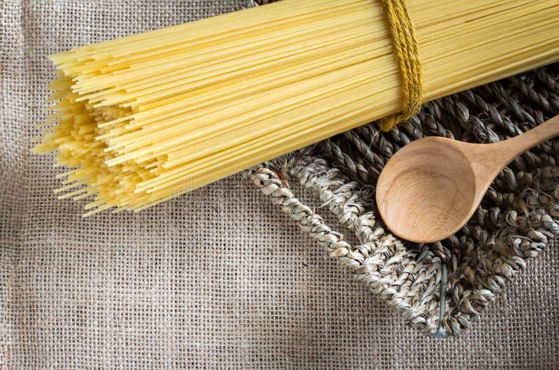 Ongekookte spaghetti en lepelhout in mand stock afbeelding