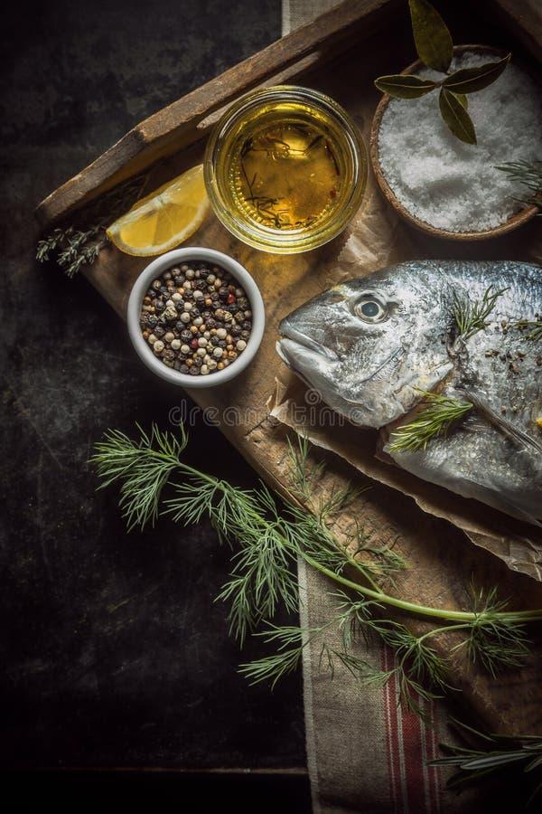 Ongekookte verse vissen met kruiden en kruiden stock foto