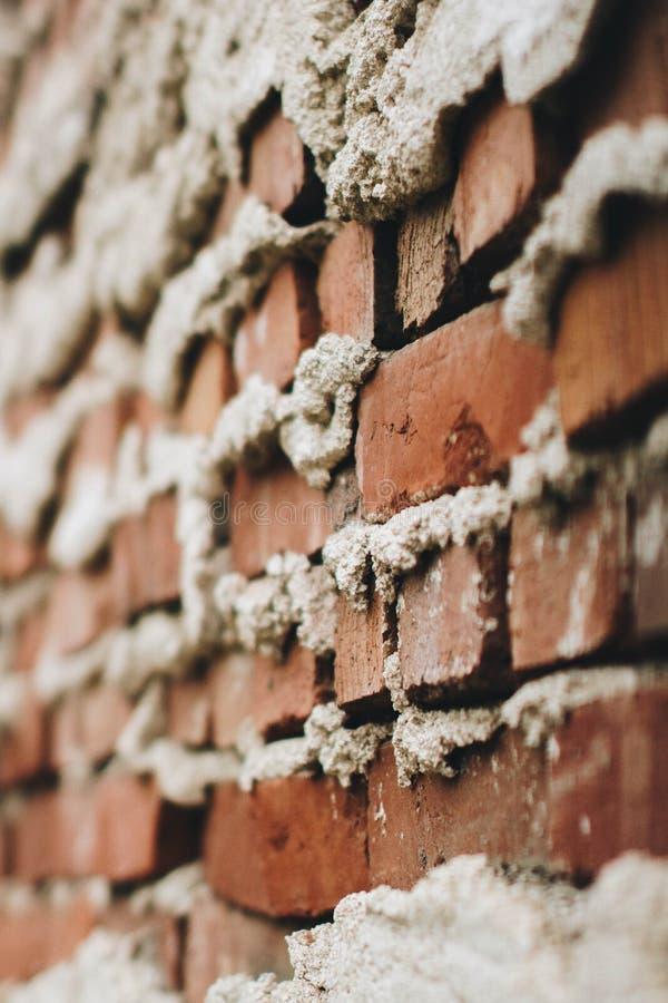 Ongelijk gebouwde bakstenen muur met cement die uit de barsten komen stock afbeeldingen