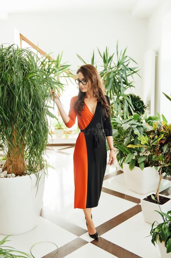Ongelooflijk mooi meisje met glazen in de tuin met installaties stock foto