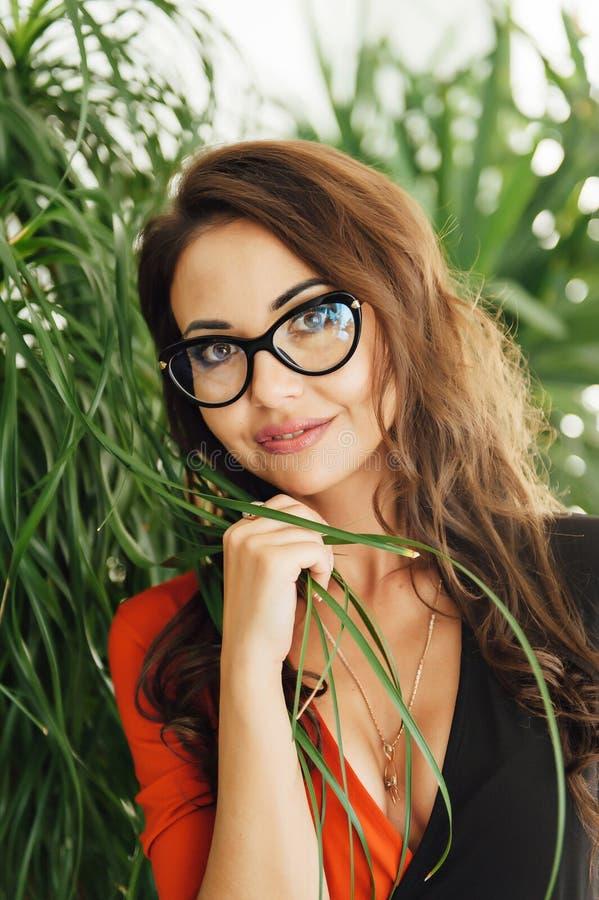 Ongelooflijk mooi meisje met glazen in de tuin met installaties stock afbeelding