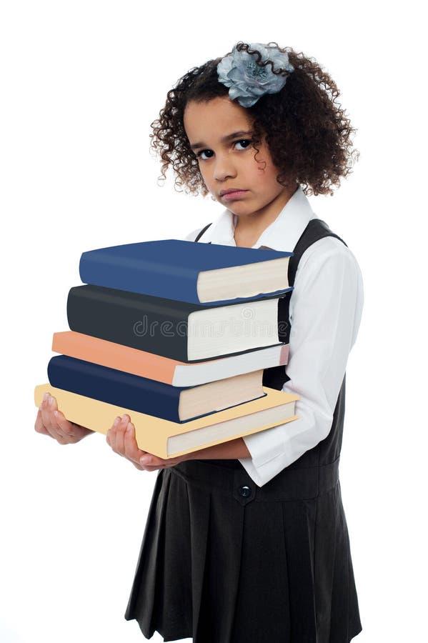 Ongelukkig schoolmeisje met stapel van boeken royalty-vrije stock foto's