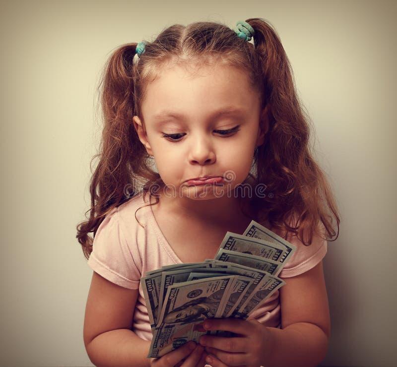 Ongelukkig verward grimassen trekkend jong geitjemeisje die op dollars in handen kijken royalty-vrije stock foto's