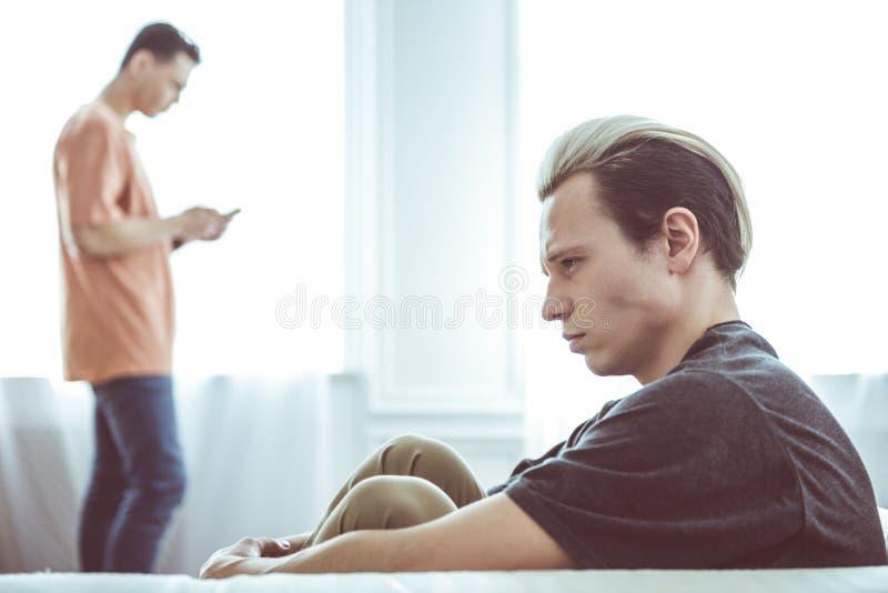 Ongelukkig vrolijk paar die aan elkaar na argument thuis spreken niet stock fotografie