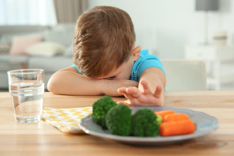 Ongelukkig weinig jongen die groenten bij lijst weigeren te eten stock afbeelding