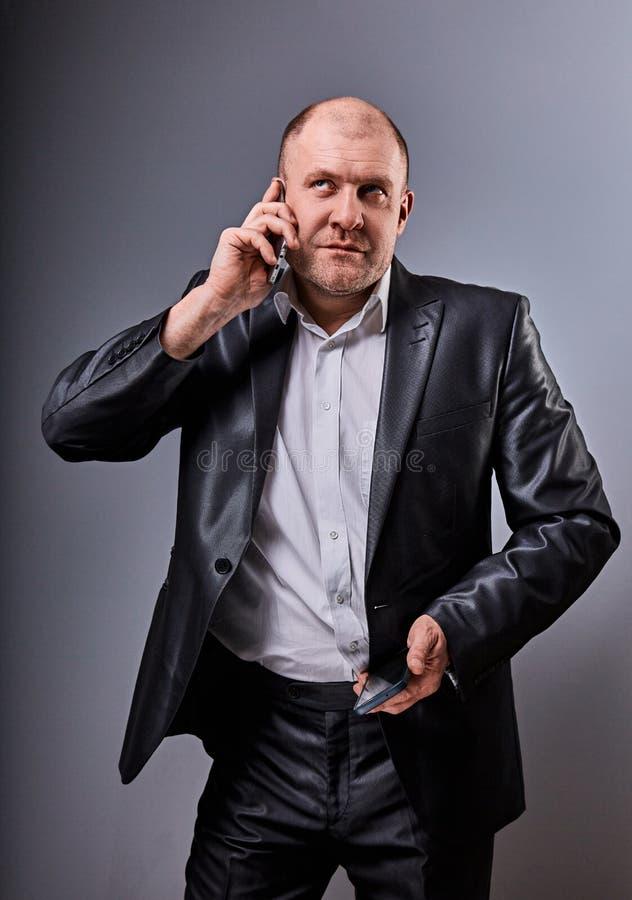 Ongelukkige beklemtoonde boze bedrijfsmens die op mobiele telefoon zeer emotioneel in bureaukostuum spreken en omhoog op grijze s stock foto's