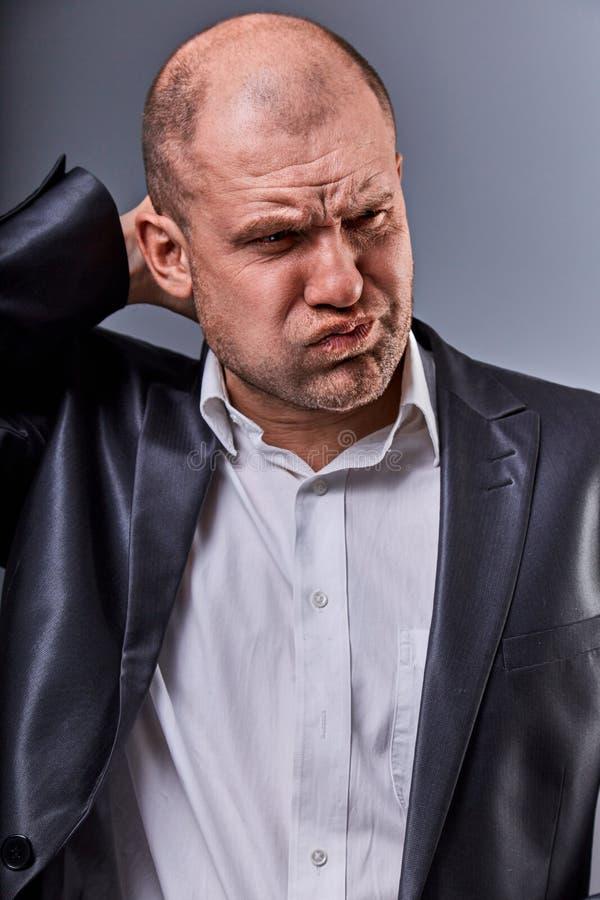 Ongelukkige beklemtoonde kale boze bedrijfsmens die het hoofd met zeer slechte emoties in bureaukostuum houden op grijze studioac stock foto's