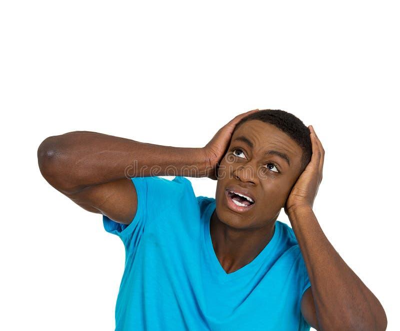 Ongelukkige beklemtoonde mens die zijn oren behandelen die omhoog eruit zien royalty-vrije stock afbeeldingen