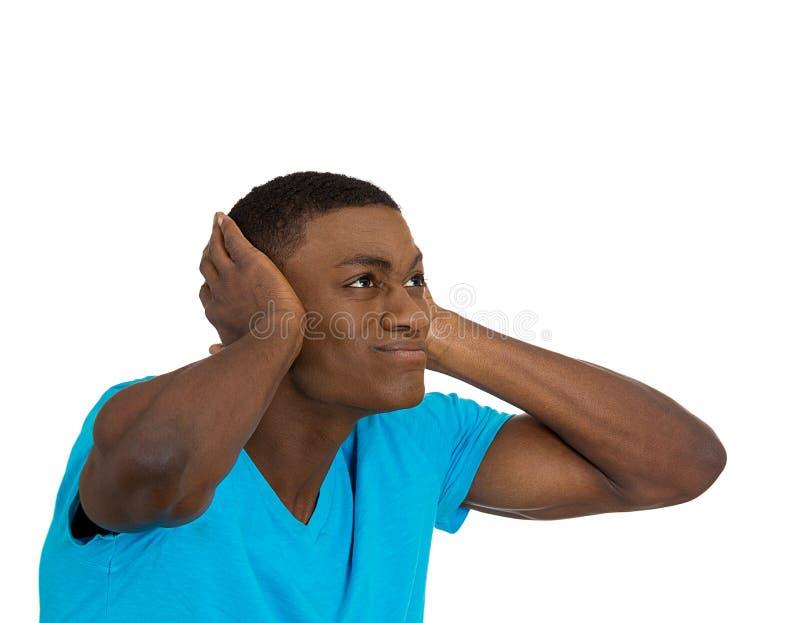 Ongelukkige beklemtoonde mens die zijn oren behandelen die omhoog eruit zien stock foto's