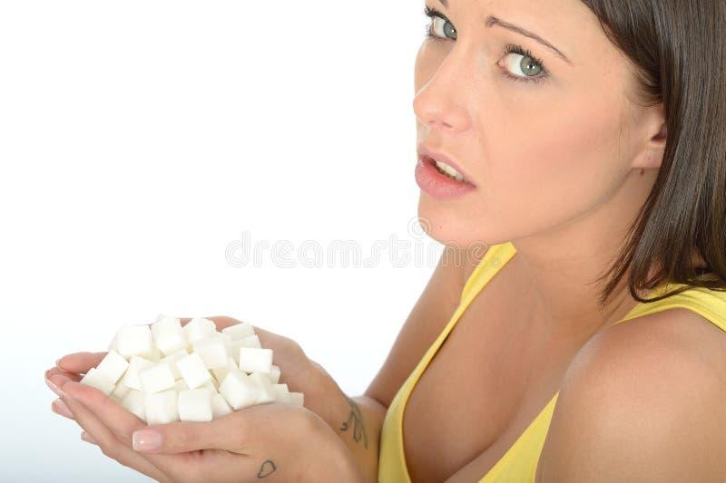 Ongelukkige Betrokken Jonge Vrouw die een Handvol van Ongezond Wit Sugar Cubes houden stock foto