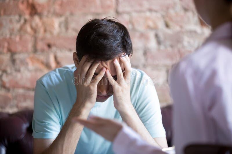 Ongelukkige jonge mens bij een ontvangst van de psycholoogadviseur royalty-vrije stock fotografie