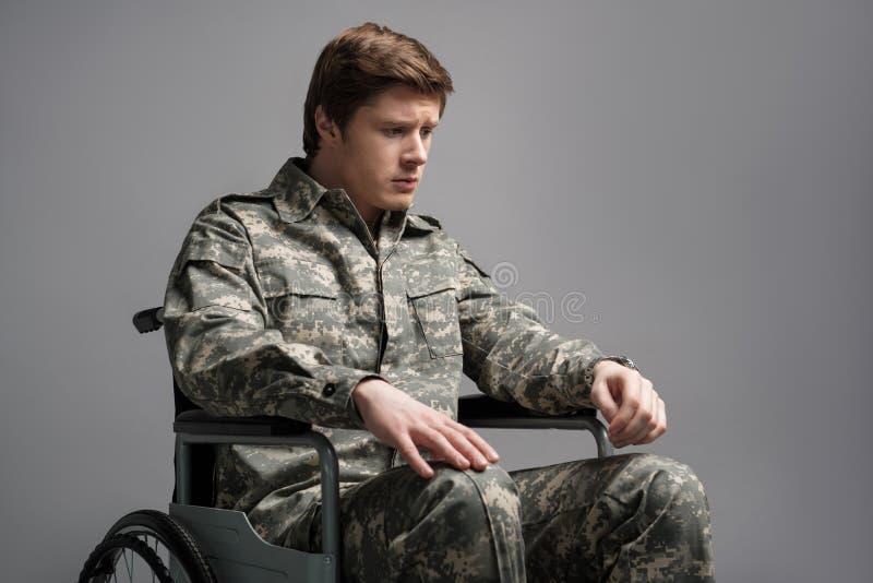 Ongelukkige jonge mens die militaire eenvormig dragen stock foto's