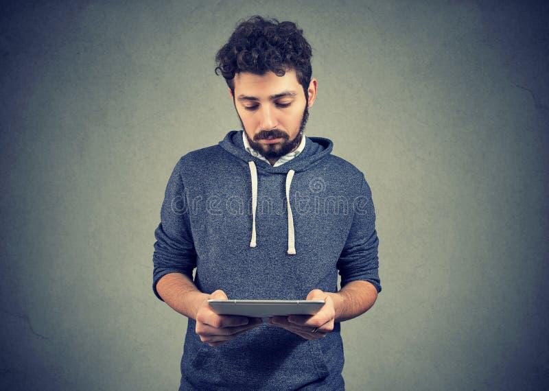 Ongelukkige jonge mens die tablet gebruiken royalty-vrije stock foto's