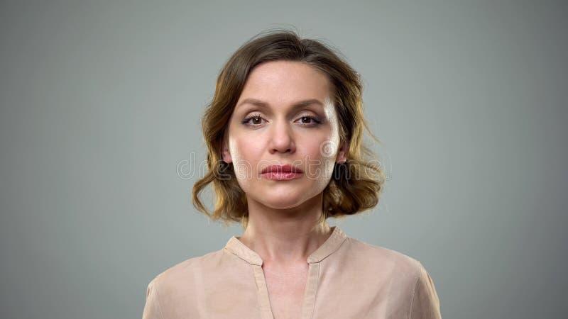 Ongelukkige jonge vrouw op grijze achtergrond, vrouwelijke eenzaamheid, verbrekendepressie royalty-vrije stock afbeeldingen