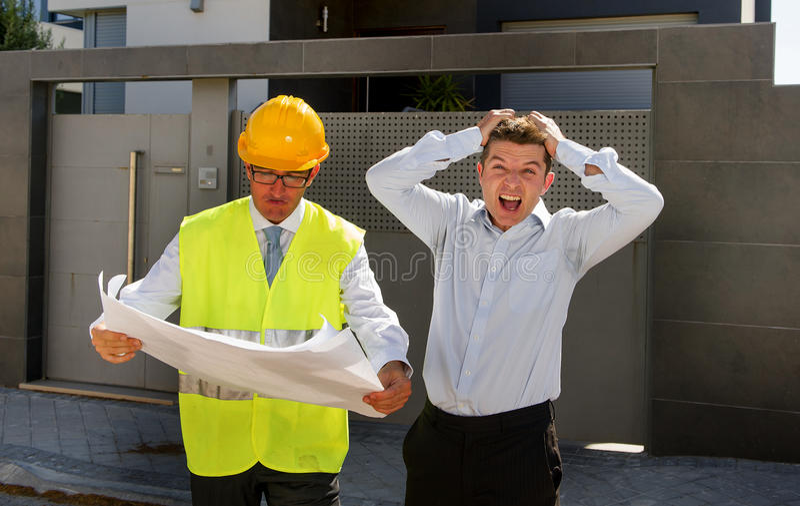 Ongelukkige klant in spanning en de arbeider van de aannemersvoorman met helm en vest die in openlucht op nieuwe woningbouwblauwd royalty-vrije stock fotografie