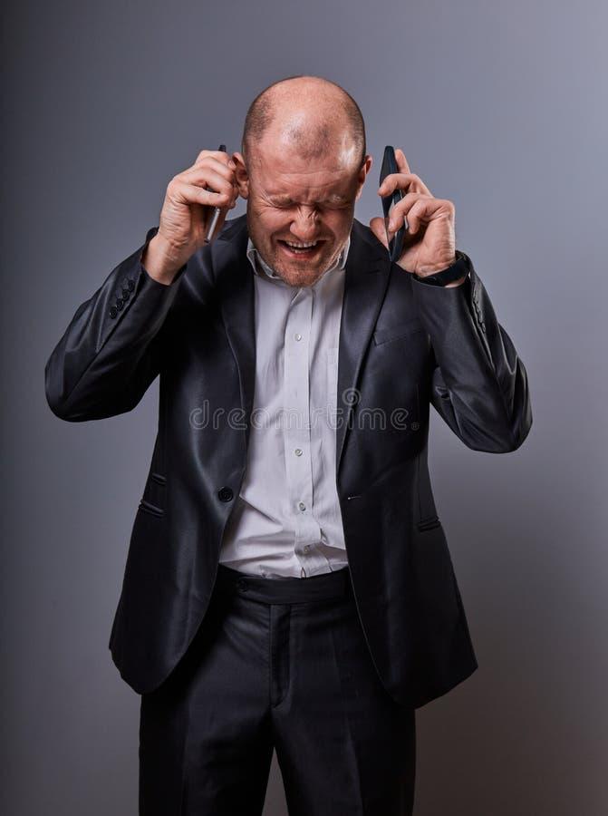 Ongelukkige luide schreeuwende woede bedrijfsmens die op twee mobiele telefoons zeer emotioneel in bureaukostuum spreken op grijz royalty-vrije stock afbeeldingen