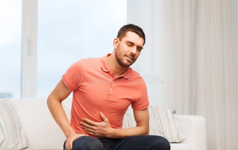 Ongelukkige mens die aan maagpijn thuis lijden stock afbeelding