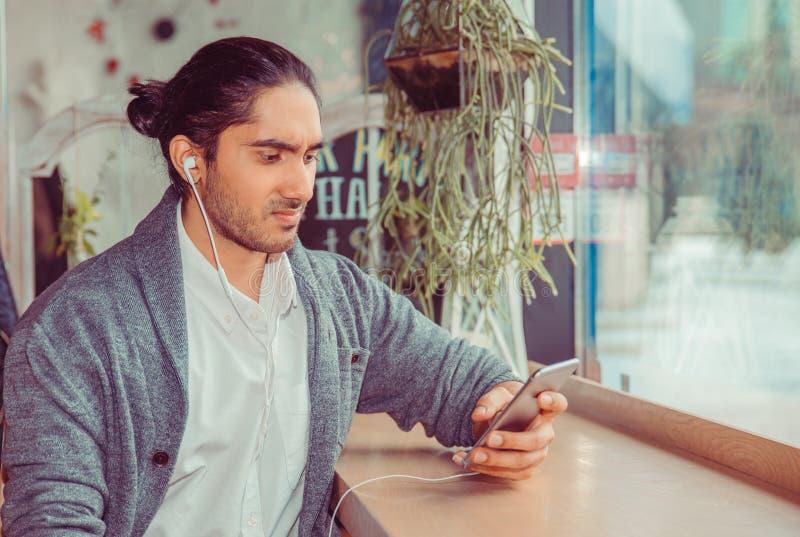 Ongelukkige mens die met oortelefoons aan een mobiele telefoon kijken stock foto's