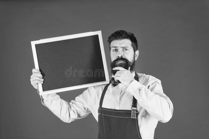 Ongelukkige mensenchef-kok met leeg bord, exemplaarruimte gebaarde hipsterkok in schort Grote keuken Het koken door recept royalty-vrije stock afbeelding