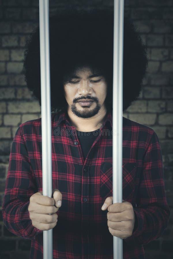 Ongelukkige misdadiger in de gevangenis stock afbeeldingen