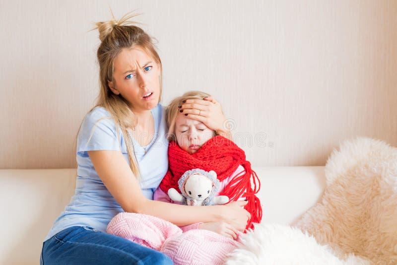 Ongelukkige moeder met ziek kind thuis stock foto