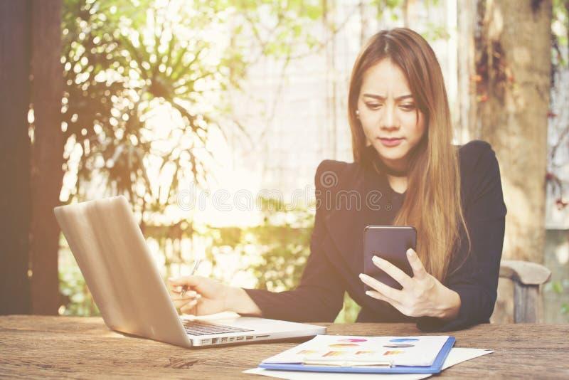 Ongelukkige ondernemer die met een telefoon en laptop in een koffie werken stock afbeelding