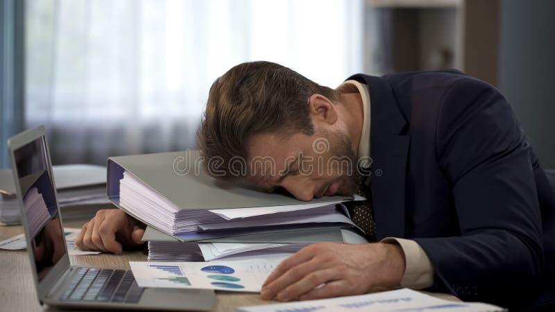 Ongelukkige overwerkte mannelijke manager die op stapel van omslagen op het werk, vermoeidheid liggen stock fotografie