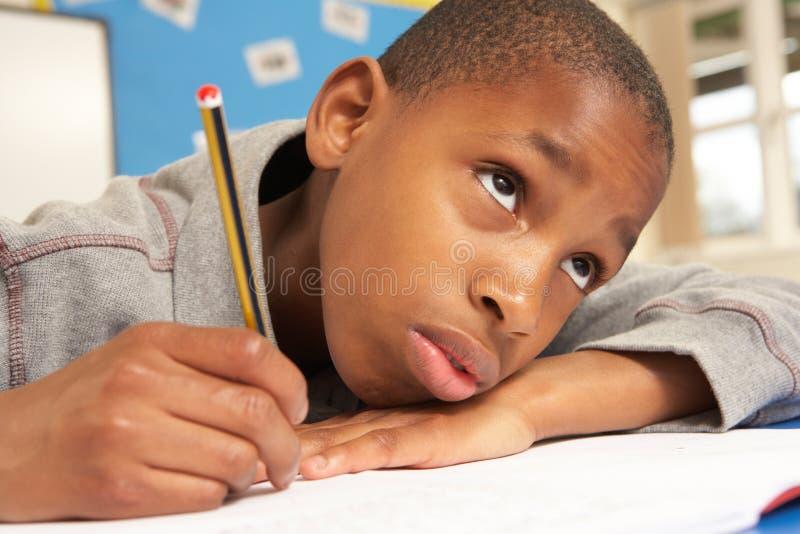 Ongelukkige Schooljongen die in Klaslokaal bestudeert royalty-vrije stock afbeelding