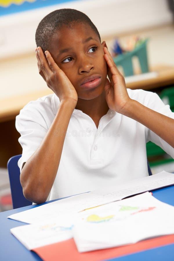 Ongelukkige Schooljongen die in Klaslokaal bestudeert royalty-vrije stock foto's