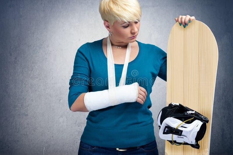 Ongelukkige snowboarder met gebroken wapen stock foto's