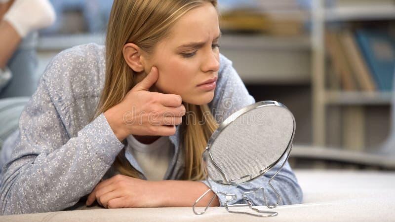 Ongelukkige tiener die haar problematische huidvoorwaarde bekijken, zelf-kritiek royalty-vrije stock afbeelding