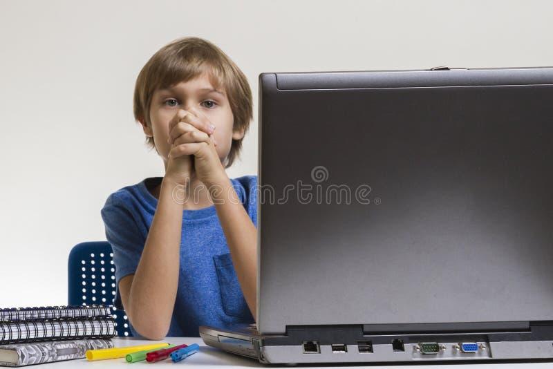 Ongelukkige vermoeide bored jongenszitting dichtbij laptop PC stock foto