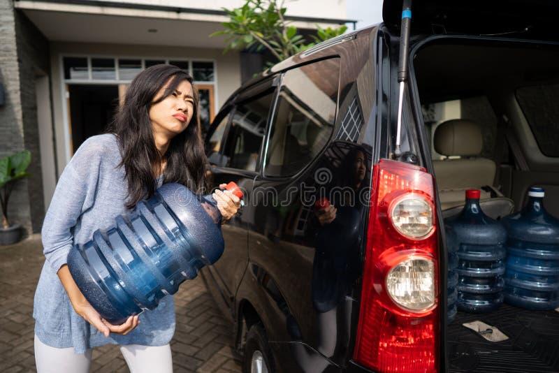 Ongelukkige vrouw die een gallon water dragen royalty-vrije stock afbeeldingen