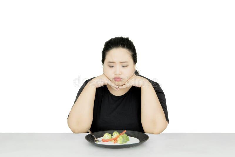 Ongelukkige vrouw die gezond voedsel op studio eten royalty-vrije stock foto