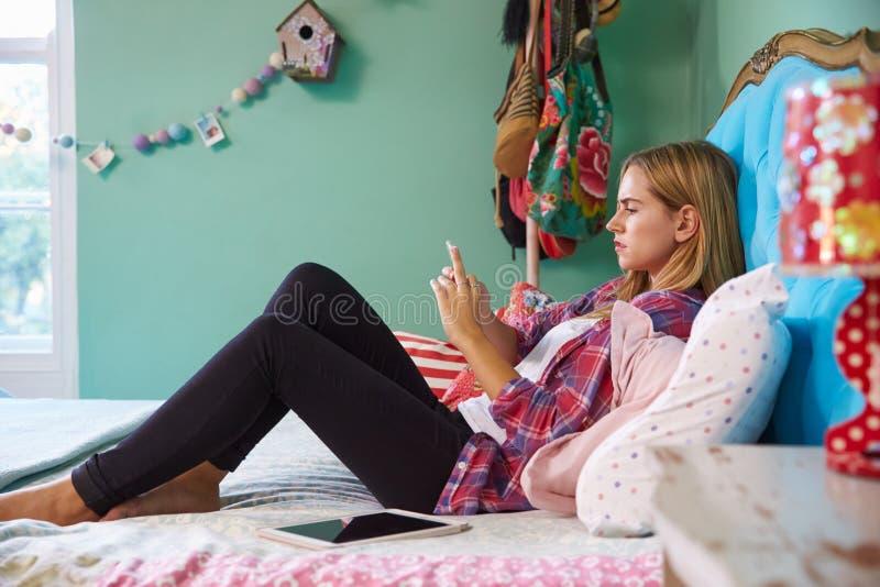 Ongelukkige Vrouw die op Bed liggen die thuis Mobiele Telefoon met behulp van royalty-vrije stock afbeeldingen