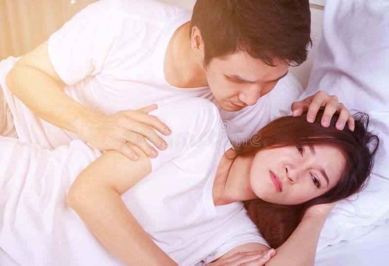 Ongelukkige vrouw die op bed met een betrokken kerel liggen die haar troosten stock afbeelding