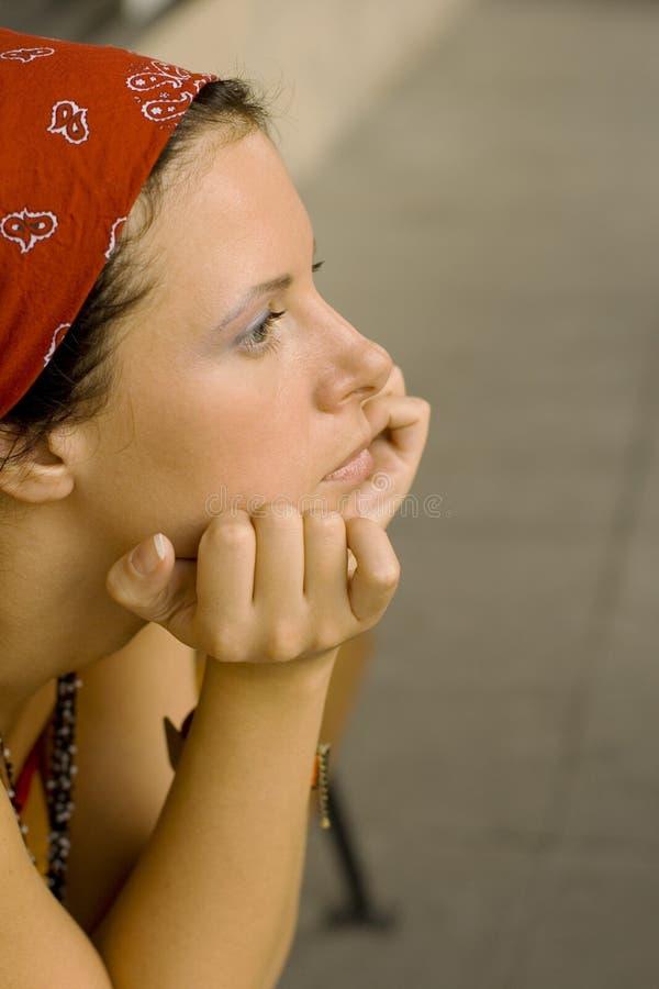 Ongelukkige vrouw in rode hoofddoek stock afbeeldingen