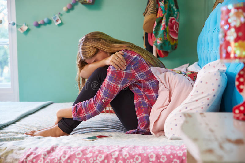 Ongelukkige Vrouwenzitting op Bed thuis stock afbeeldingen