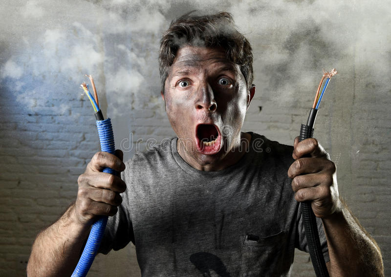 Ongeoefende mens die zich bij elektrokabel aansluiten die aan elektroongeval met vuil gebrand gezicht in grappige schokuitdrukkin stock foto