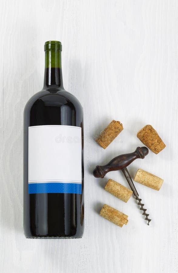 Ongeopende grote fles rode wijn met een antieke kurketrekker en royalty-vrije stock afbeelding
