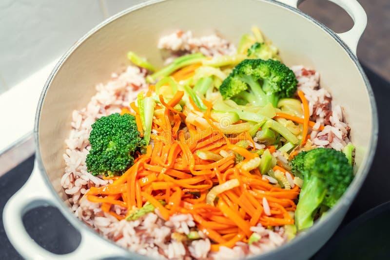 Ongepelde rijst met organische onvermengde gepelde gesneden groenten die in gietijzersteelpan koken Heldere broccoli, wortel en royalty-vrije stock foto