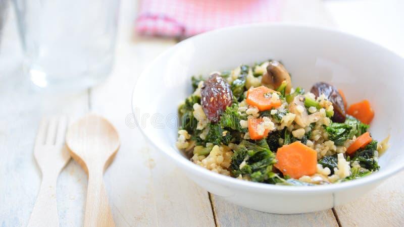 Ongepelde rijstsalade met sommige groenten, noten en zaden Maaltijd op een witte houten lijst in een landelijk restaurant wordt g royalty-vrije stock fotografie