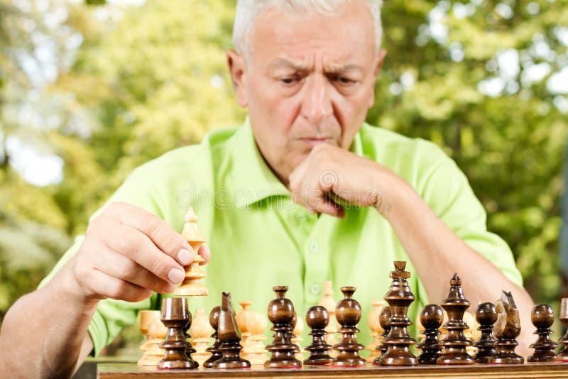 Ongerust gemaakt bejaarde het spelen schaak in openlucht stock fotografie