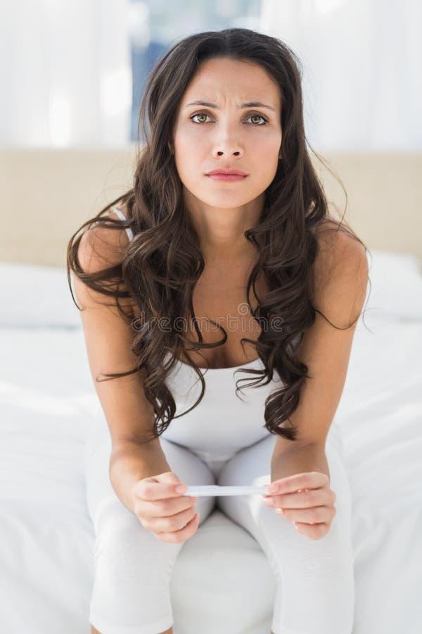 Ongerust gemaakt Donkerbruin wachten op zwangerschapstest royalty-vrije stock afbeelding