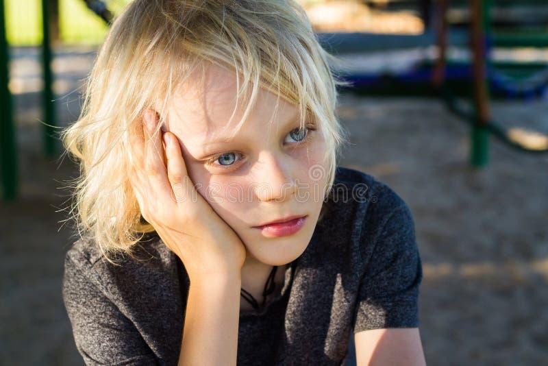 Ongerust gemaakt, droevig kind alleen in schoolspeelplaats stock foto's