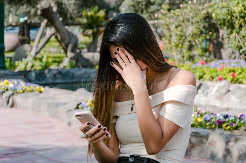 Ongerust gemaakt Hipster-tienermeisje die haar slimme telefoon in een park bekijken stock afbeelding